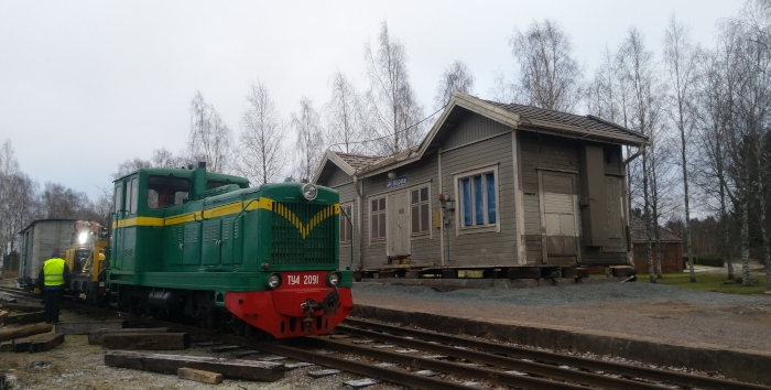 A wooden station building with a work train and a green diesel locomotive.